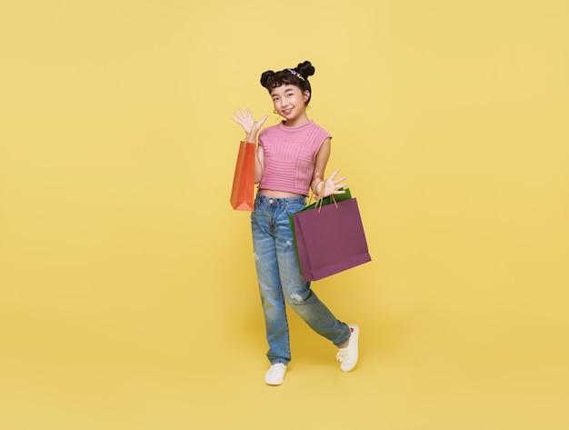 Wesoły szczęśliwe dziecko azjatyckie dziecko korzystające z zakupów, ona niesie torby na zakupy w centrum handlowym.