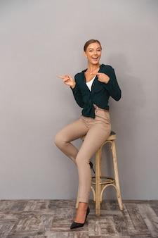 Wesoły szczęśliwy biznes kobieta stojąca na białym tle nad szarym tle ściany wskazując.
