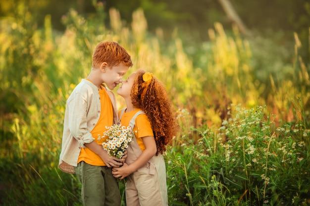 Wesoły szczęśliwy brat i siostra dzieci na spacerze po lesie z bukietem stokrotek.
