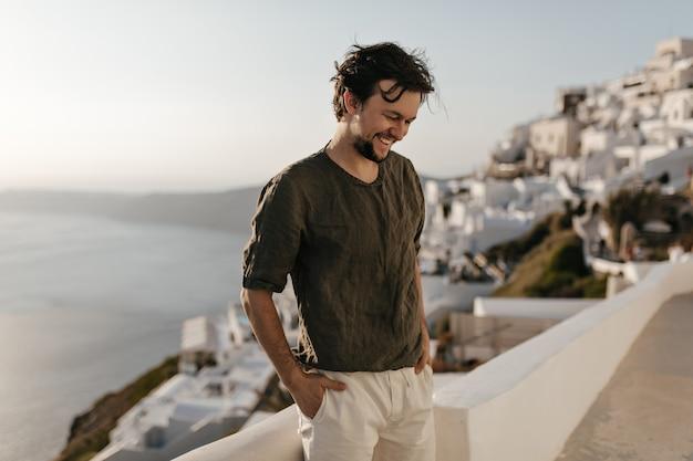 Wesoły szczęśliwy brunetka mężczyzna w ciemnozielonej koszulce i białych spodenkach szczerze uśmiecha się na zewnątrz