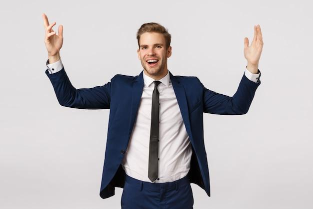 Wesoły szczęśliwy i odnoszący sukcesy przedsiębiorca w klasycznym garniturze, podnoszący ręce zachwycony, osiągający cel, świętujący dobrą ofertę, zwiększony dochód, zadowolony, odczuwający ulgę