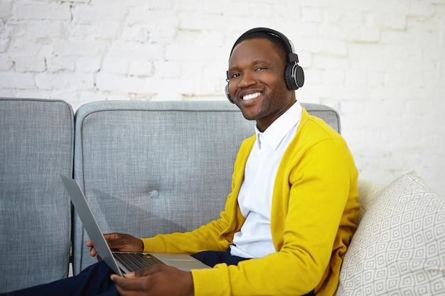 Wesoły szczęśliwy młody afroamerykanin mężczyzna w swobodnym stroju korzystający z nowoczesnych urządzeń elektronicznych w domu, słuchając ulubionej muzyki za pomocą słuchawek bezprzewodowych i laptopa, relaksując się na kanapie