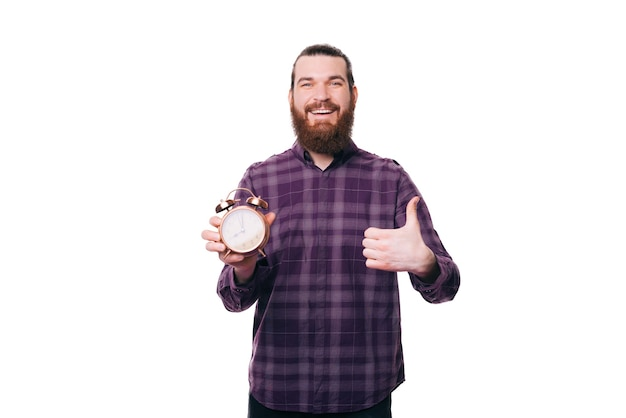 Wesoły szczęśliwy przystojny brodaty mężczyzna pokazuje kciuk i budzik