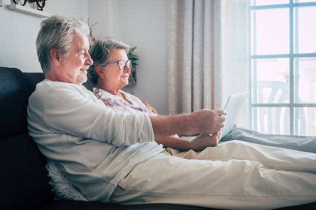 Wesoły szczęśliwy starszych para starszych ludzi w domu patrząc na komputer razem położył się na kanapie ciesząc się życiem razem