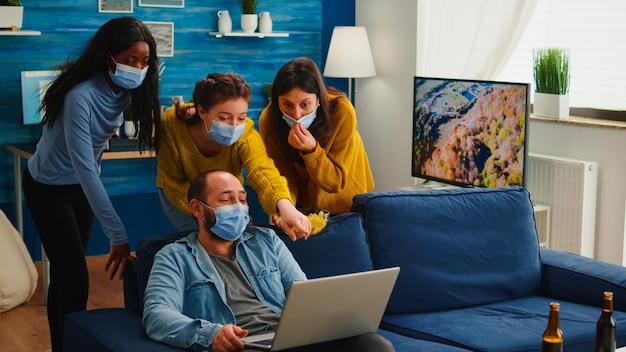 Wesoły, szczęśliwy, wieloetniczny przyjaciele patrzący na zdjęcie na laptopie, bawiący się razem, zachowując dystans społeczny, nosząc maskę na twarz, zapobiegając rozprzestrzenianiu się koronawirusa. różnorodni ludzie cieszą się nową normalną imprezą