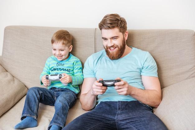 Wesoły tata i syn grają razem w gry komputerowe w domu