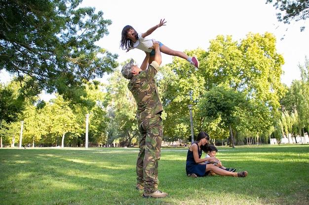 Wesoły tata podnosi córkę i stoi na trawniku. szczęśliwy ojciec bawi się z wychodzącą dziewczyną w parku. brunetka mama i synek siedzi na trawie. zjazd rodzinny i koncepcja powrotu do domu