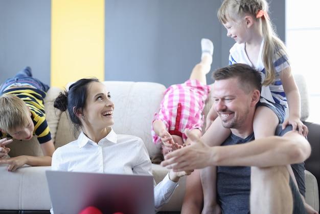 Wesoły tata trzyma córkę na szyi. wesoła mama trzyma na kolanach szarego laptopa i patrzy na córkę