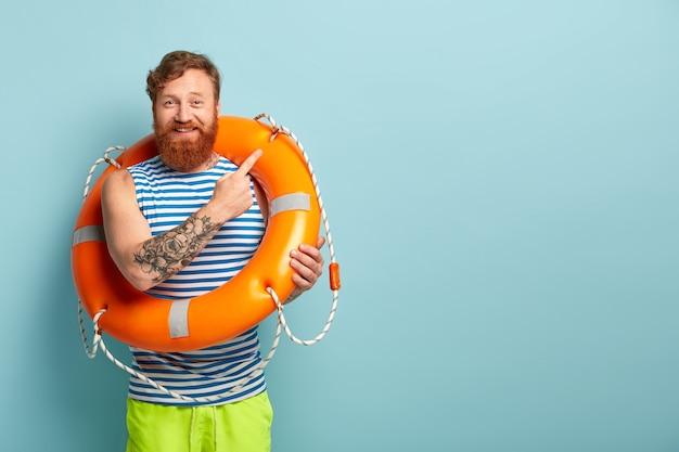 Wesoły trener pływania lub instruktor niesie na ciele linę ratunkową, prowadzi lekcje bezpiecznego pływania