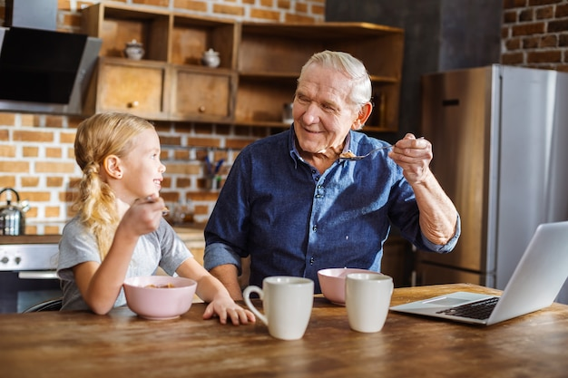 Wesoły, troskliwy starszy mężczyzna je śniadanie ze swoją śliczną małą wnuczką