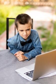 Wesoły uczeń chłopiec jest zaangażowany w lekcje przez laptopa w domu w ogrodzie. zajęcia online dla dzieci