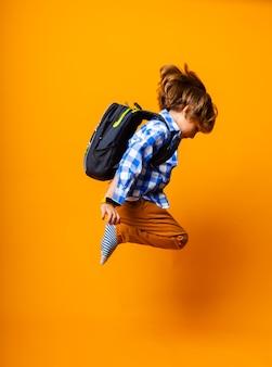 Wesoły uczeń w plecaku skaczącym na żółtym tle. dynamiczne obrazy. powrót do szkoły.