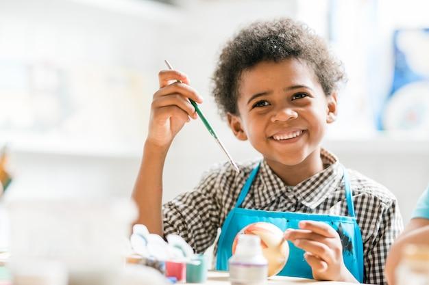 Wesoły uczeń z pędzlem robiącym świąteczną zabawkę na lekcji, myśląc o tym, komu dać ją jako prezent