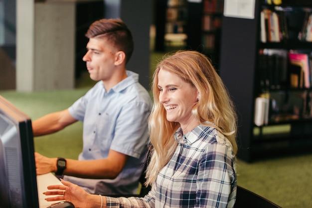 Wesoły uczniowie na komputerach