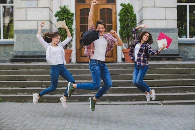 Wesoły uczniowie skaczą z podniecenia