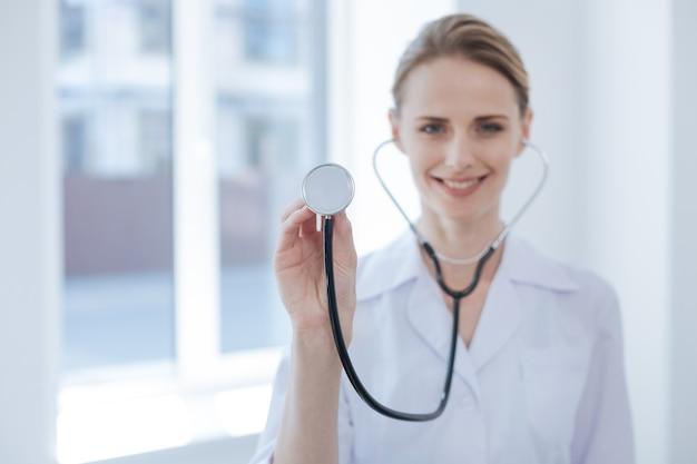 Wesoły, uroczy, doświadczony lekarz pracujący w szpitalu w oczekiwaniu na nowego pacjenta i wyrażający zachwyt