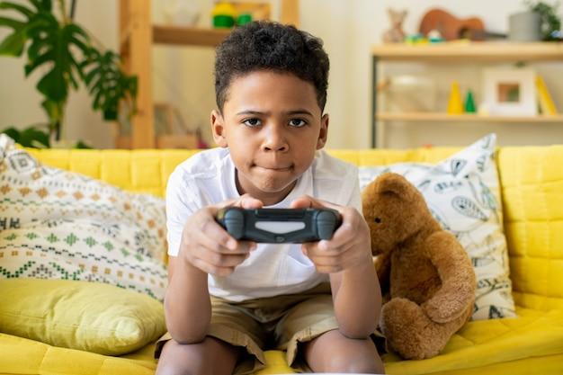 Wesoły, uroczy mały chłopiec pochodzenia afrykańskiego z joystickiem patrząc na ciebie z uśmiechem, grając w grę wideo na kanapie w wolnym czasie
