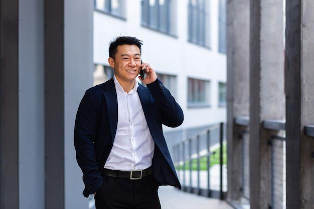 Wesoły uśmiech odnoszący sukcesy azjatycki biznesmen wyjaśnia informacje pracownikom za pomocą telefonu, rozmawia w pobliżu biura na zewnątrz szczęśliwej rozmowy