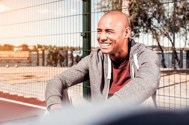 Wesoły uśmiech. wesoły, radosny człowiek będący w świetnym nastroju siedząc na boisku sportowym