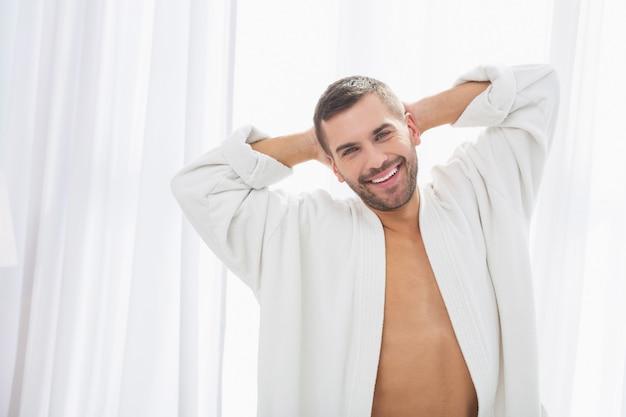 Wesoły uśmiech. zachwycony pozytywny człowiek będący w świetnym nastroju podczas odpoczynku w domu