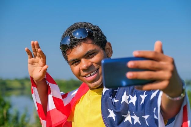 Wesoły uśmiechnięty african american młody człowiek w okularach przeciwsłonecznych i pokryte amerykańską flagą biorąc selfie na zewnątrz.