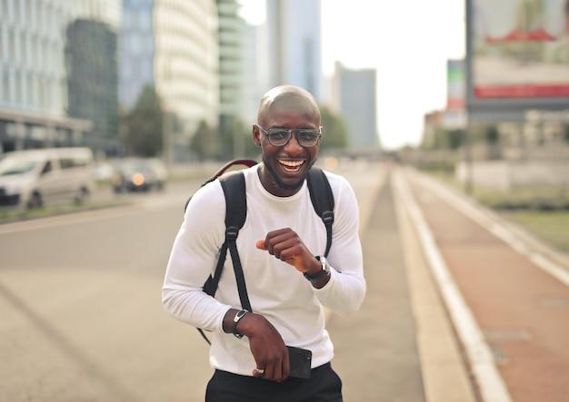 Wesoły uśmiechnięty afrykański mężczyzna w okularach ubrany w białą koszulkę i plecak na ulicy