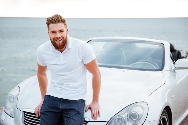 Wesoły, uśmiechnięty brodaty mężczyzna stojący przy swoim nowym samochodzie na plaży
