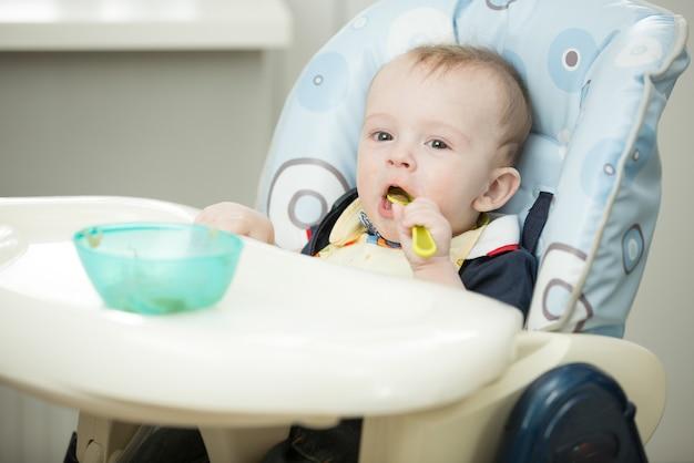Wesoły uśmiechnięty chłopiec bawi się łyżką w krzesełku