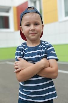 Wesoły uśmiechnięty chłopiec z dużą niebieską czapką w szkole