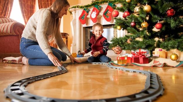 Wesoły uśmiechnięty chłopiec z młodą matką buduje kolej wokół choinki w salonie. dziecko otrzymujące prezenty i zabawki w nowy rok lub boże narodzenie