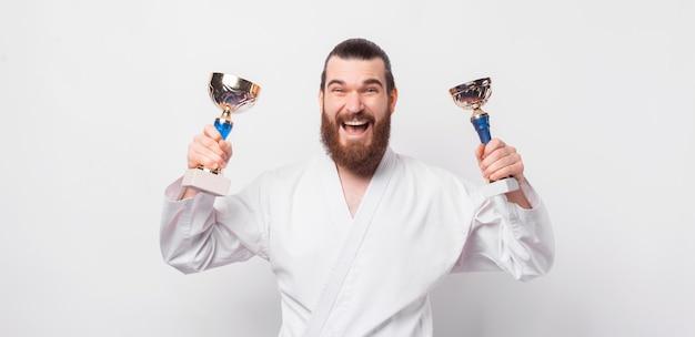 Wesoły, uśmiechnięty mężczyzna z brodą w mundurze taekwondo i świętuje z dwoma złotymi pucharkami