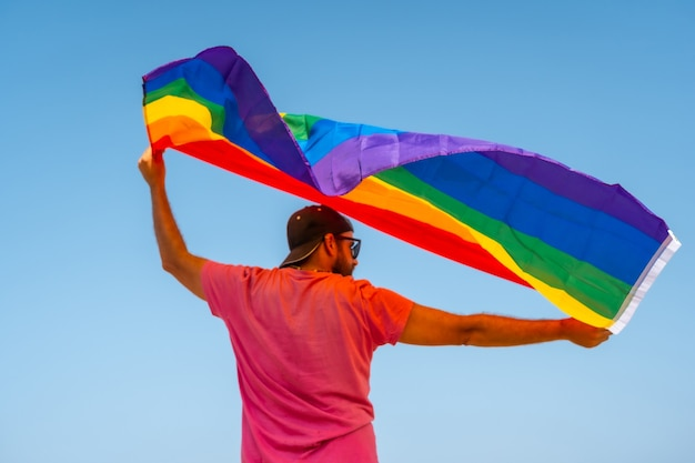 Wesoły w różowej koszulce i czarnej czapce z flagą lgbt na plecach poruszającą się z wiatrem z niebem w tle, symbolem homoseksualizmu