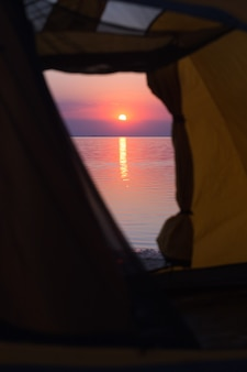 Wesoły weekend nad morzem - namiot na tle zachodu słońca i sylwetki dzieci spacerujących po morzu. ukraiński krajobraz nad morzem azowskim, ukraina