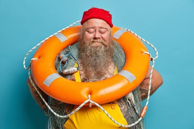 Wesoły, wesoły, brodaty rybak stoi z zamkniętymi oczami, trzymając nadmuchane pomarańczowe koło ratunkowe, spędzając wolny czas w pozach łodzi rybackich