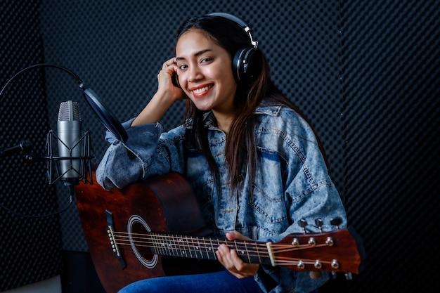 Wesoły wesoły ładny uśmiech portret młodej azjatyckiej wokalistki noszącej słuchawki z gitarą nagrywającej piosenkę przed mikrofonem w profesjonalnym studiu