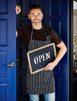 Wesoły właściciel małej firmy z otwartym znakiem