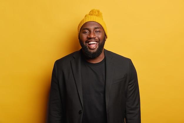 Wesoły zabawny mężczyzna, ubrany w czarny garnitur i żółtą czapkę zimową z pomponem, pozytywnie się uśmiecha, stoi w domu.