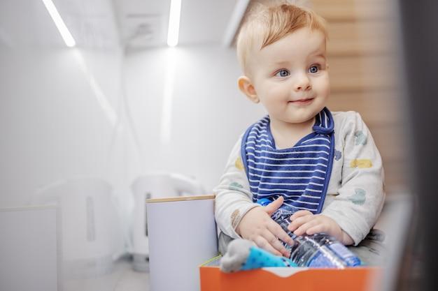 Wesoły zadowolony kaukaski mały chłopiec siedzi w pudełku na blacie kuchennym i bawi się butelką wody.