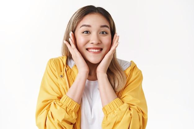 Wesoły zadowolony ładny błyszczący uśmiechnięty szczęśliwy azjatycki blond dziewczyna dotyk policzków zaskoczony otrzymanie pozytywnych wspaniałych wiadomości wyrażone podekscytowanie zachwycony uśmiech zachwycony wdzięczny triumf, biała ściana
