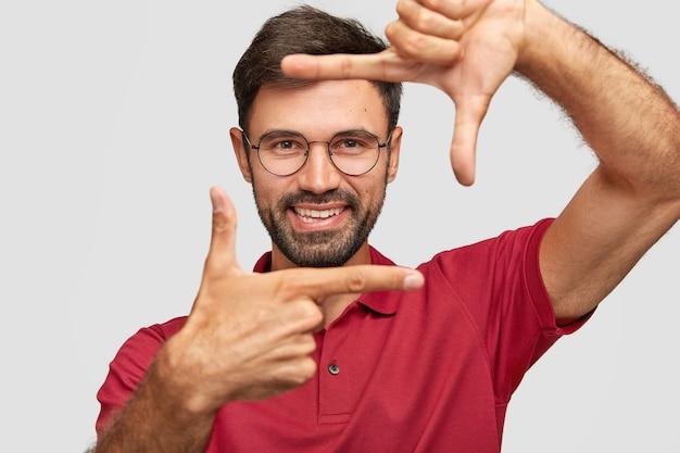 Wesoły zadowolony nieogolony mężczyzna robi obiema rękami znak ramki, przygotowuje się do fotografowania