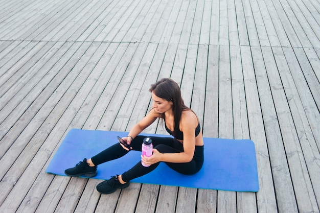 Wesoły zdrowy fitness kobieta w odzieży sportowej siedzi na macie do jogi i rozmawia w smartfonie na świeżym powietrzu na drewnianych deskach