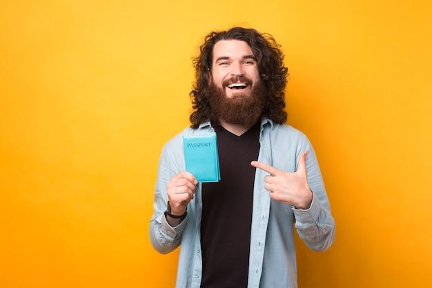Wesoły zdumiony brodaty hipster wskazujący na paszport na żółtym tle, jedziemy w podróż