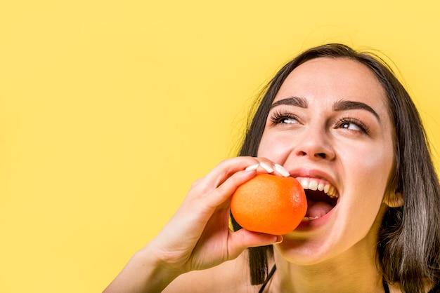 Wesoły żeński gryzący mandarynka