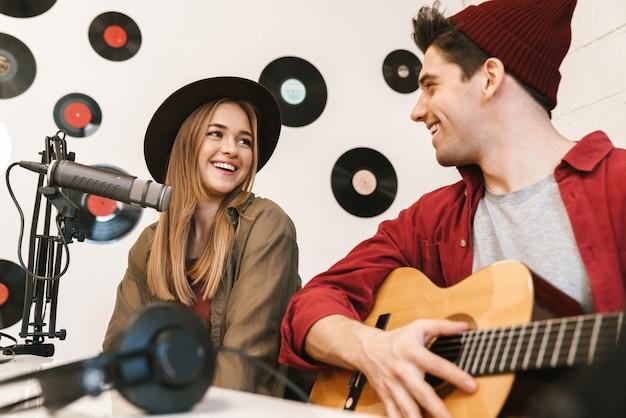 Wesoły zespół młodych muzyków grających swoją piosenkę w sali radiowej, audycja radiowa