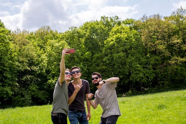 Wesoły znajomi biorący selfie na polanie