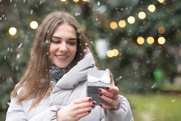 Wesołych blond kobieta trzyma pudełko podczas opadów śniegu. pusta przestrzeń