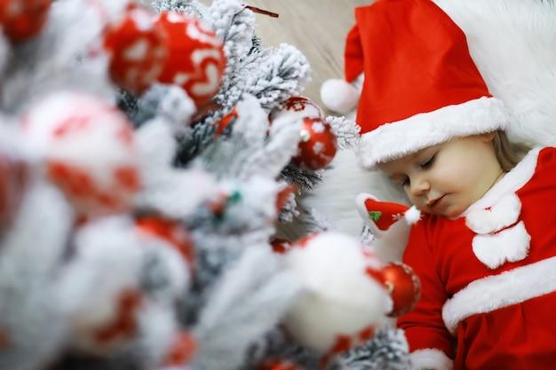Wesołych jasnych świąt. urocze dziecko cieszy się świętami bożego narodzenia. wspomnienia z dzieciństwa. santa dziewczynka małe dziecko świętuje boże narodzenie w domu. rodzinne wakacje. dziewczyna słodkie dziecko wesoły nastrój grać w pobliżu choinki.