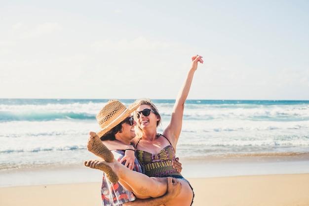 Wesołych ludzi szczęśliwa młoda para uśmiecha się i śmieje się razem bawiąc się na plaży w letnie wakacje
