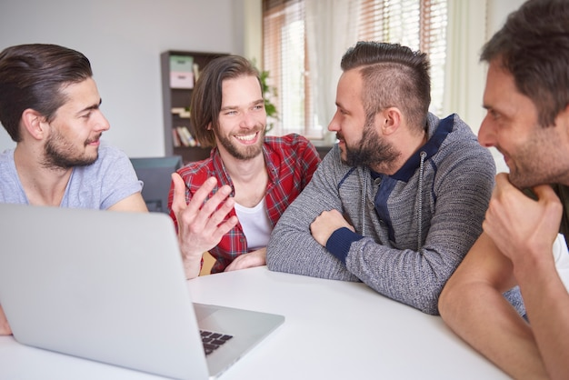 Wesołych mężczyzn siedzących przed laptopem