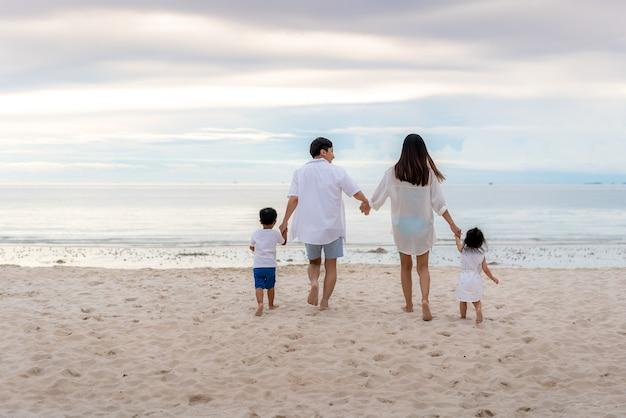 Wesołych rodzinnych wakacji podczas radosnych spacerów ojca, matki, syna i córki wzdłuż morza o zachodzie słońca latem. szczęśliwa rodzina podróż na plaży w wakacje, lato i wakacje.